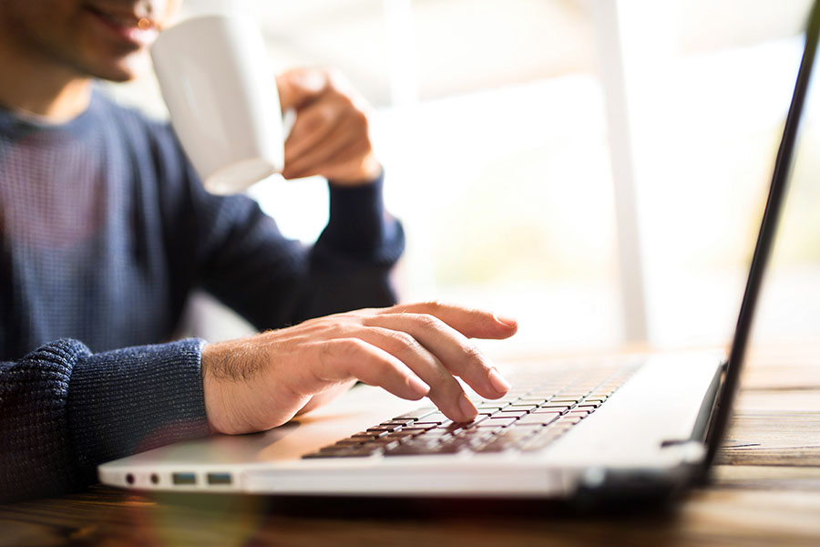 Blog - Man Sitting at Home Drinking Coffee and Using a Laptop