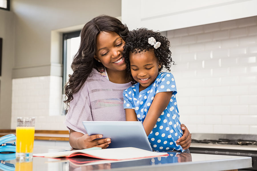 Client Portal - Smiling Mother and Daughter Standing in Kitchen Using a Tablet